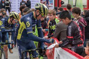 Ciclista dándole un autógrafo a un niño