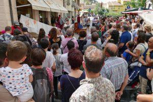 Personas viendo una espectáculo en la calle